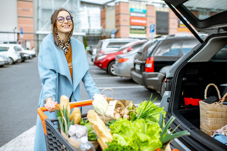 Foto de Young woman with shopping cart full of fresh and healthy food on the parking place near the supermarket - Imagen libre de derechos