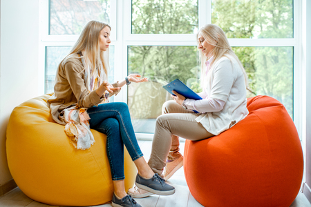 Photo pour Young woman with senior female psychologist or mental coach sitting on the comfortable chairs during the psychological counseling in the office - image libre de droit