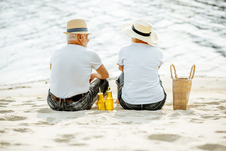 Photo pour Senior couple sitting together with drinks and bag on the sandy beach, enjoying their retirement near the sea, rear view - image libre de droit