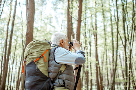 Foto de Senior man looking with binoculars while traveling with backpack in the forest - Imagen libre de derechos