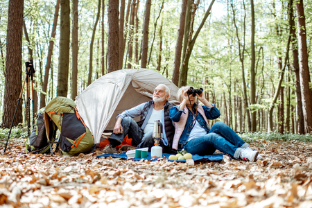 Photo pour Senior couple sitting together at the campsite with tent and backpacks, enjoying nature with binoculars in the forest - image libre de droit