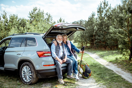 Photo pour Senior couple sitting at the car trunk, enjoying nature while traveling in the young pine forest - image libre de droit