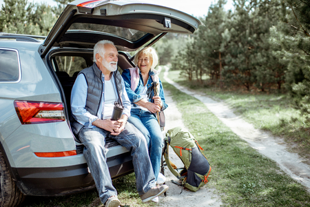 Foto de Senior couple sitting at the car trunk, enjoying nature while traveling in the young pine forest - Imagen libre de derechos