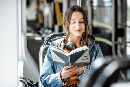 Photo pour Young woman reading book while moving in the modern tram, happy passenger at the public transport - image libre de droit