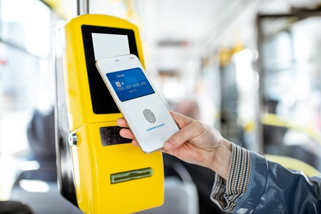 Foto de Paying conctactless with smartphone for the public transport in the tram, close-up view - Imagen libre de derechos