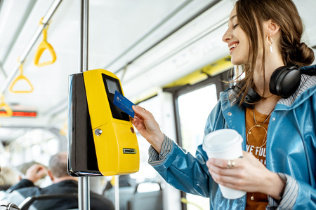 Photo pour Woman paying conctactless with bank card for the public transport in the tram - image libre de droit