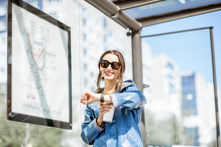Photo pour Young woman checking time while standing at the tram station outdoors - image libre de droit