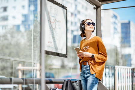 Photo pour Young stylish woman waiting for the public transport while standing at the modern tram station outdoors - image libre de droit