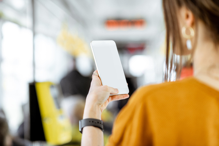 Foto de Woman holding phone with empty screen to copy paste while standing in the tram - Imagen libre de derechos