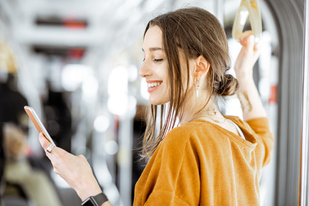 Photo pour Close-up portrait of a young woman using smartphone while standing in the modern tram - image libre de droit