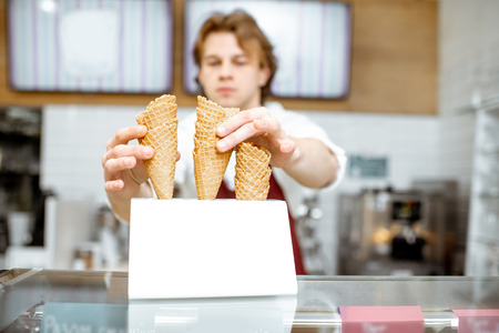 Photo pour Handsome salesman taking waffle cone while making ice cream for the client in the modern pastry shop - image libre de droit