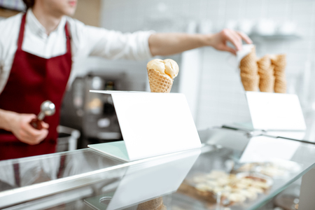 Foto de Ice cream in the waffle cone on the counter of the pastry shop with salesperson on the background - Imagen libre de derechos