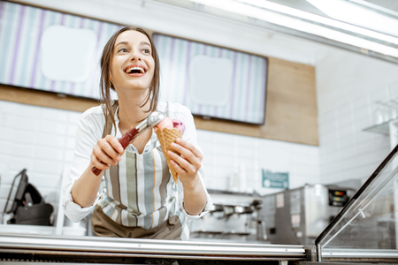 Photo pour Young and happy saleswoman in apron making ice cream at the counter of the modern pastry shop indoors - image libre de droit