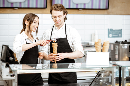 Photo pour Man and woman making ice cream in waffle cones for selling, standing together at the counter of the modern shop - image libre de droit