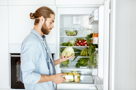 Photo pour Young vegan man choosing what to cook, taking fresh vegetables from the refrigerator at home - image libre de droit