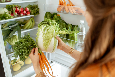 Woman taking fresh cabbage and carrot from the refrigerator at home, close-up view