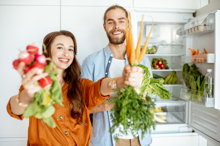 Foto de Portrait of a young and happy couple standing with fresh vegetables near the refrigerator full of healthy products at home - Imagen libre de derechos