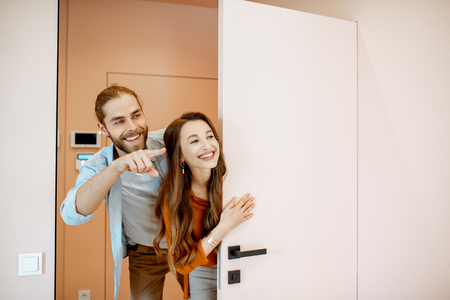Photo for Portrait of a young couple looking out the door at the corridor of the new modern apartment. Concept of happy real estate owners - Royalty Free Image