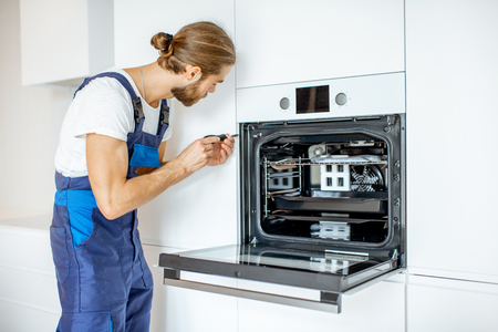 Photo pour Handsome workman in workwear installing electric oven into the kitchen shelves at the modern kitchen at home - image libre de droit