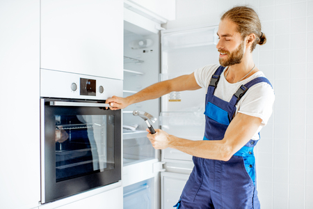 Photo pour Workman checking the strength of the glass oven door with a hammer at home - image libre de droit