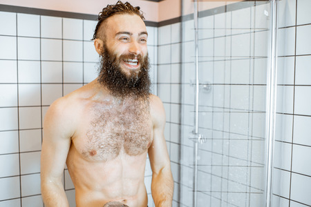 Photo pour Bearded man feeling shocked while taking a shower with cold water in the bathroom at home - image libre de droit