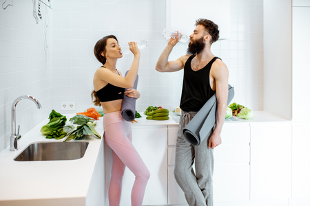 Foto de Young couple in sportswear having a break after the yoga training, drinking water at the kitchen with healthy food at home - Imagen libre de derechos
