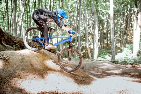 Photo pour Professional well equipped cyclist riding downhill on the off road in the forest. Concept of an extreme sport and enduro cycling - image libre de droit