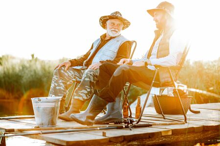 Photo pour Grandfather with adult son fishing together on the wooden pier during the morning light. View from the side of the lake - image libre de droit