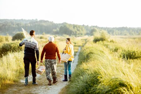 Photo pour Young man and woman walking on the picnic with senior grandfather dressed in sweaters, spending a good time together on the nature - image libre de droit