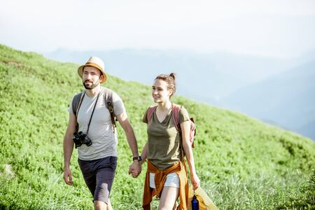 Photo for Beautiful couple walking with backpacks on the green valley, while traveling high in the mountains during the summer time - Royalty Free Image