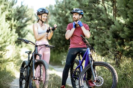 Photo for Man and woman cyclists wearing gloves and helmet, preparing for the bicycle riding while standing on the forest road during the summer time - Royalty Free Image