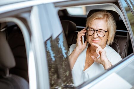 Photo pour Senior business woman talking with phone while sitting on the back seat of the modern car. Concept of a business life on retirement - image libre de droit