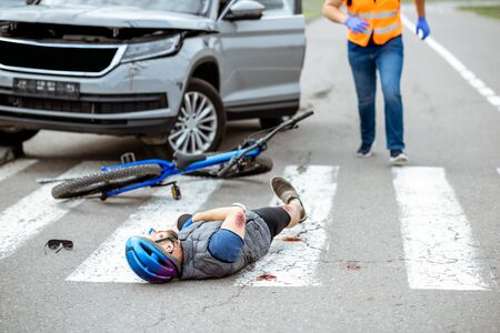 Foto de Road accident with injured cyclist lying on the pedestrian crossing near the broken bicycle and car driver running on the background - Imagen libre de derechos