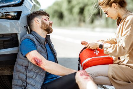 Foto de Driver hurrying with first aid kit to help injured man with bleeding wounds sitting near the car after the road accident - Imagen libre de derechos