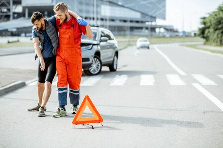 Photo pour Medic in uniform helping injured man to walk, applying first aid after the road accident - image libre de droit