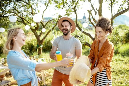 Photo pour Young friends having fun, standing together with drinks in the beautifully decorated backyard or garden during a festive lunch or party - image libre de droit