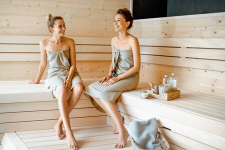 Two young girlfriends sitting and talking together while relaxing in the sauna. Concept of female friendship and spa treatment