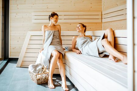 Two young girlfriends covered with sheets relaxing in the luxury sauna. Concept of female friendship and spa treatment
