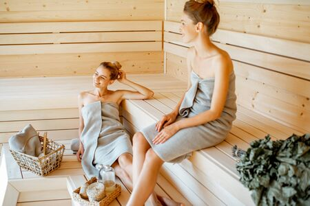 Two young girlfriends wrapped in sheets relaxing in the sauna. Concept of female friendship and spa treatment