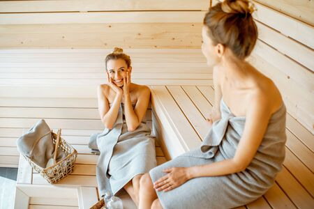 Two young girlfriends relaxing in the sauna, sitting together and taking care of themselves. Concept of female friendship and spa treatment