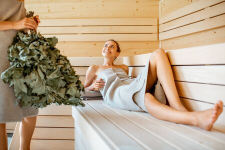 Two young girlfriends relaxing in the sauna, holding bath broom and talking together