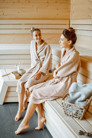 Two young beautiful girlfriends in bathrobes sitting together while relaxing in the luxury sauna