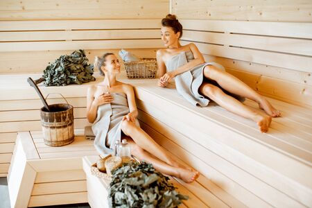 Photo pour Two young girlfriends relaxing in the sauna, lying on the wooden benches with bucket and bath brooms - image libre de droit