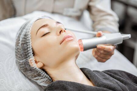 Foto de Woman during the oxygen mesotherapy procedure at the beauty salon, close-up view. Concept of a professional facial treatment - Imagen libre de derechos