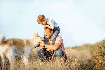 Photo for Portrait of a happy father with young son riding on the shoulders and their dog having fun on the field. Concept of a happy family on a summer activity - Royalty Free Image