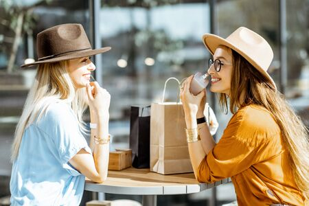 Photo for Two stylish girlfriends sitting at the modern cafe terrace outdoors, looking on a new purchases after the shopping - Royalty Free Image
