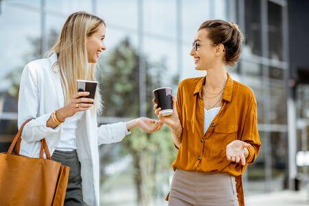 Foto de Two young businesswomen talking near the office building, having a small talk during the coffee break outdoors. - Imagen libre de derechos