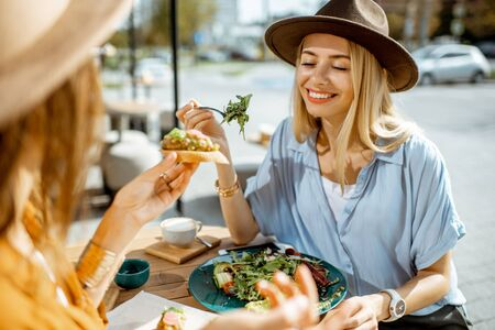 Photo pour Two female best friends eating healthy food while sitting together on a restaurant terrace on a summer day - image libre de droit