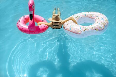 Photo pour Woman in swimsuit and hat swimming with inflatable toys in the water pool, enjoying vacations during the summer time - image libre de droit