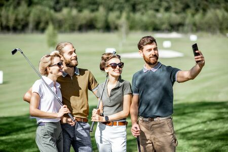 Photo pour Group of young and happy friends making selfie photo while standing together with golf putters during a game on the golf course - image libre de droit